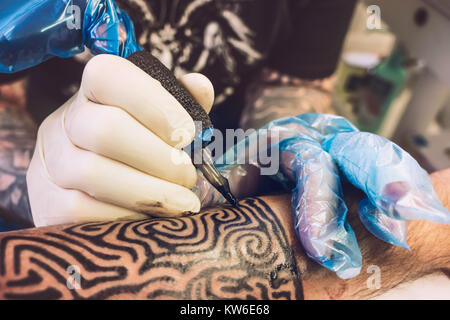 Close-up of a professional tattooist with gloves tattooing a tribal design on the left forearm of a costumer, France. - Stock Photo