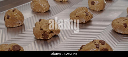 A close up of raw chocolate chip cookie dough, rolled into balls on a baking sheet - Stock Photo