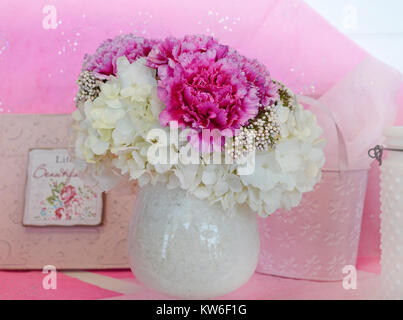 Floral arrangement with white hydrangea and pink peonies in a white vase against a soft pastel background. - Stock Photo