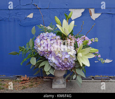 Vintage floral arrangement against a peeling blue background. Hydrangea and lilies in a stone urn. - Stock Photo