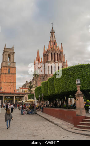 The beautiful pink Gothic Parroquia de San Miguel Arcangel towering above the El Jardin, with tourists and vendors, - Stock Photo