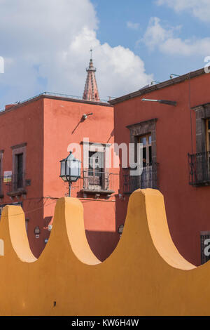 A portion of the yellow outer wall of Bellas Artes, shaped like a wave, a two story old red building, the tip of - Stock Photo
