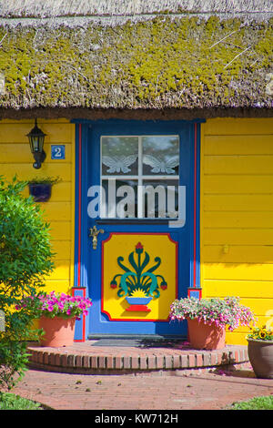 Colourful painted frontdoor of a thatched-roof house at village Born at Darss, Fischland, Mecklenburg-Western Pomerania, - Stock Photo