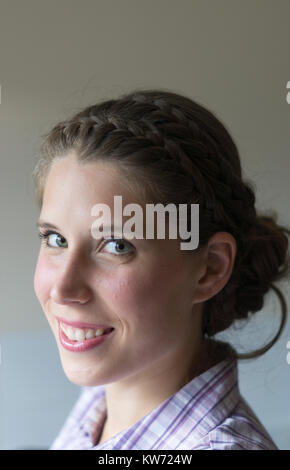A young woman with braided hair in her twenties looking sideways on at the viewer - Stock Photo