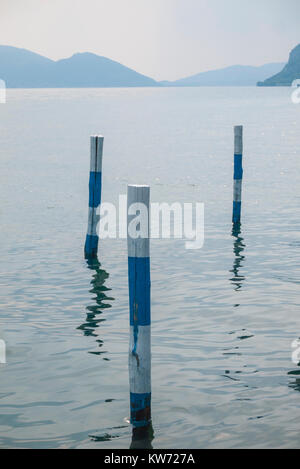 Striped mooring poles at a dock at Lake Iseo in Italy - Stock Photo