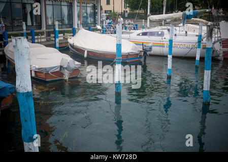 Boats moored on the jetty by Lake Iseo, Italy - Stock Photo