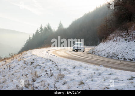 Silver car on an icy road in winter. Country road beside Ladybower reservoir in the Derwent Valley, Derbyshire, - Stock Photo