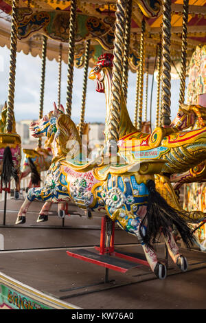 Colourful painted horses in the evening sun on a carousel on Brighton Pier - Stock Photo