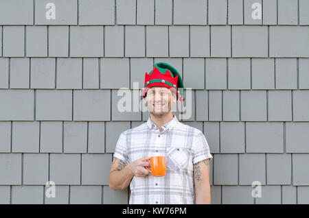 Smiling man with a Christmas hat holding a mug. - Stock Photo