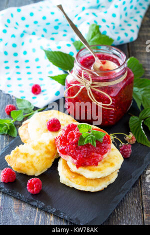 Cottage cheese fritters, pancakes with raspberry jam and fresh raspberries on a wooden rustic table. Background - Stock Photo