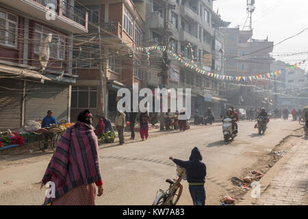 People in cold dusty streets of wintertime Kathmandu, Nepal - Stock Photo