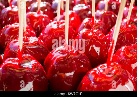 sweet glazed red toffee candy apples on sticks for sale on farmer market or country fair Stock Photo