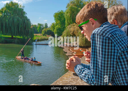 Cambridge UK punting, on a summer afternoon a young tourist on Silver Street Bridge in Cambridge watches people - Stock Photo
