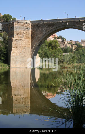 Reflection of San Martin's Bridge in Toledo, Spain in the Tagus river - Stock Photo