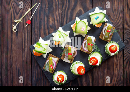 Snack canape with prawns, feta cheese and herring on rye bread on a wooden table. Flat lay. Top view. - Stock Photo
