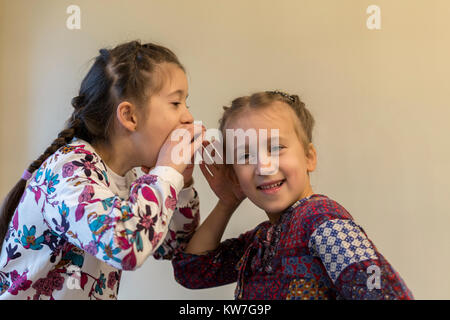 Young girl whispering secrets to her best friends ear - Stock Photo