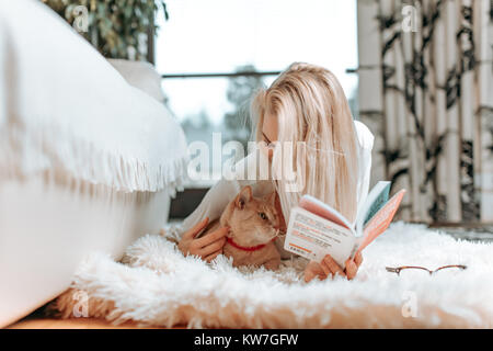 Beautiful young blonde female student studying or reading a fascinating book novel, on her white, leather sofa - Stock Photo
