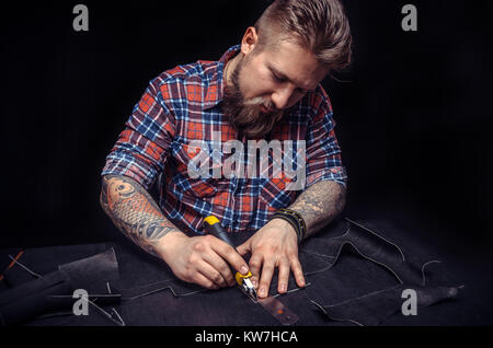 Leather workman focusing on his work  - Stock Photo