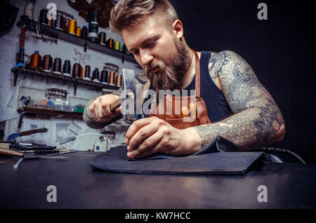 Close up of a shoemaker man working with leather using crafting tools - Stock Photo