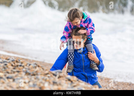 Child on woman's shoulders collecting shells on a beach on a rough day in the UK. - Stock Photo