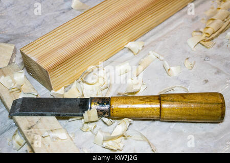 A chisel on the table among the shavings. Nearby there is a wooden bar. Selective focus - Stock Photo
