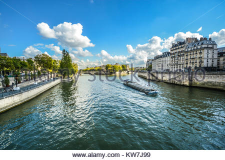 Sunny day view from the Pont d'Arcole near Ile de la Cite as a cruise boat floats down the River Seine - Stock Photo