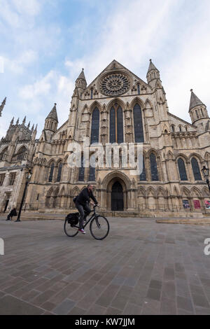 York centre - under blue sky, man riding bike across piazza, cycles past south entrance to magnificent York Minster - Stock Photo