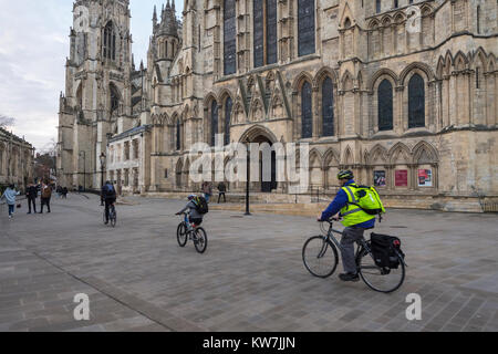 York centre - 2 adults & 1 child riding bikes, cycle across piazza, past south entrance to magnificent York Minster - Stock Photo