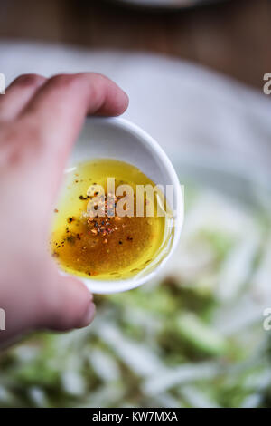 Cup with sesoning. Olive oil, mapple syrup, lemon juice, chilli flakes - Stock Photo