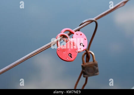 Two pink castle in the form of heart hanging on a wire - Stock Photo