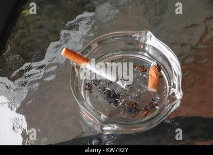 Cigarette in ashtray Placed on table glass - Stock Photo