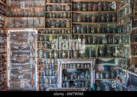 Old vintage glass bottles, jars and containers on shelves in the Ettore Guatelli etnographic museum inOzzano Taro, - Stock Photo