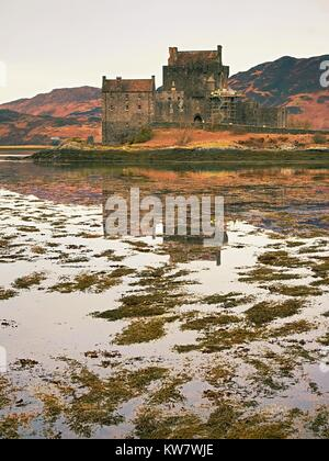 Tides in the lake at Eilean Donan Castle, Scotland. The popular stony bridge over the remnants of water with massive - Stock Photo