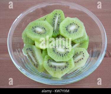 Bowl full with high in vitamins Kiwi fruit slices isolated on wooden background - Stock Photo