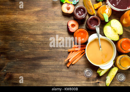 Baby food. Various purees of fruits and vegetables. On a wooden background. - Stock Photo