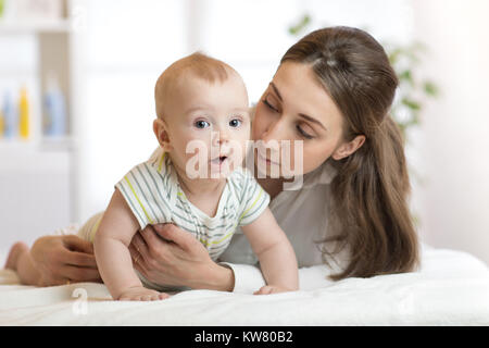 Mother and baby boy playing in sunny bedroom. Parent and little kid relaxing at home. Family having fun together. - Stock Photo