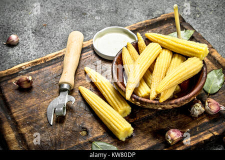 Pickled corn in a jar on a cutting board. On a rustic background. - Stock Photo
