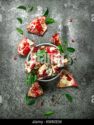 Ripe pieces of pomegranate in a bowl. On a rustic background. - Stock Photo