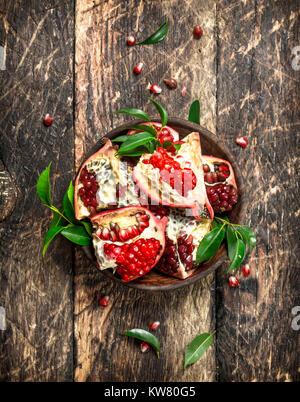 Pieces of fresh pomegranate in a bowl. On a wooden background. - Stock Photo