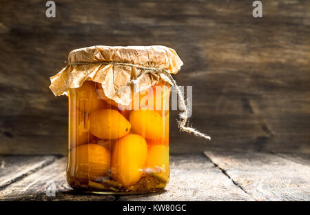 Preserves tomatoes in glass jar . On a wooden background. - Stock Photo