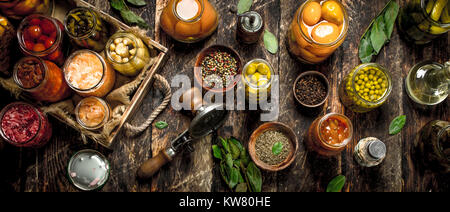 Various preserved vegetables and mushrooms with seamer and spices. On a wooden background. - Stock Photo