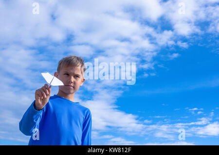 Kid holding in hand white paper plane. - Stock Photo