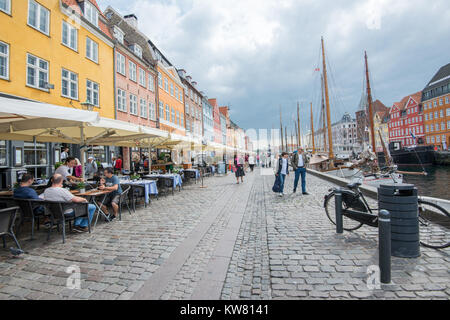 Waterfront restaurants at Nyhavn, a 17th century harbor district in the center of Copenhagen and currently a popular - Stock Photo