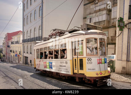 A traditional tram travelling uphill through the central streets of Alfama district Lisbon, Portugal - Stock Photo