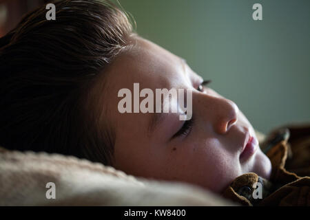 Handsome little boy with chubby cheeks and brown pompadour hair laying in bed and relaxing with the afternoon sunlight - Stock Photo