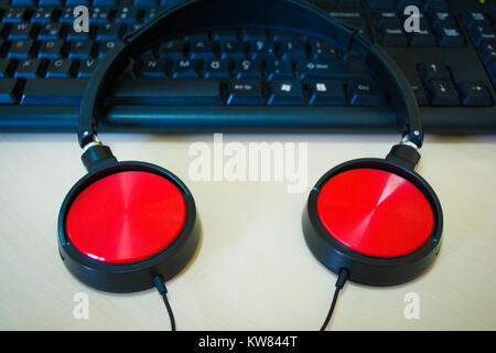 digital music creation theme with professional red headphones on the computer keyboard - Stock Photo