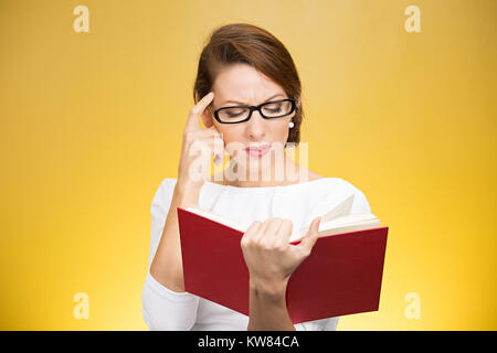 Young elegant woman in eyeglasses having problems with understanding while reading book isolated on yellow background - Stock Photo
