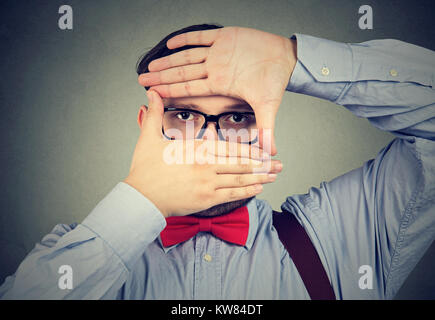 Chunky man making frame and looking at camera with limited vision. - Stock Photo