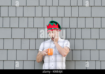 Ran out of coffee at Christmas time. Shocked man with his hand on his face holding an orange coffee mug. - Stock Photo
