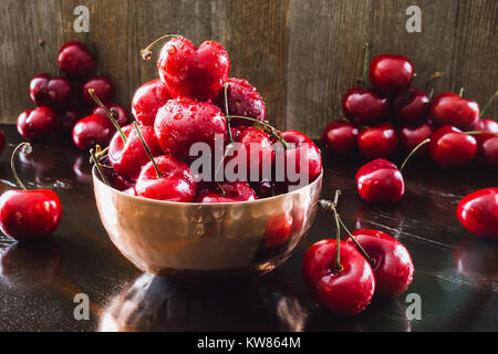 Copper Bowl of Fresh Cherries on Dark Table - Stock Photo